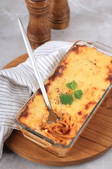 Close up spaghetti brulle on clear baking dish l with staiinless spoon and fork. spaghetti brulee is baked spaghetti with bechamel and bolognese sauce. selected focus