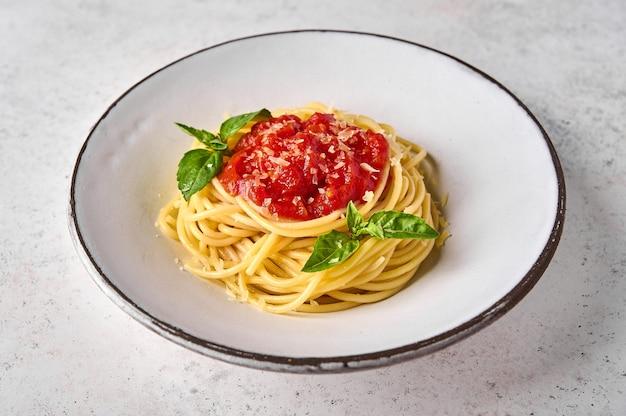 Закройте макароны спагетти в томатном соусе, сыре пармезан и базилике на белой тарелке на свете