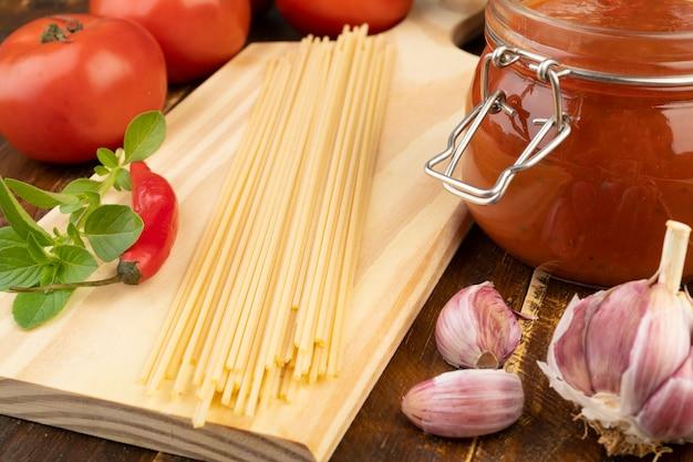 テーブルの上のトマトとスパゲッティを閉じる