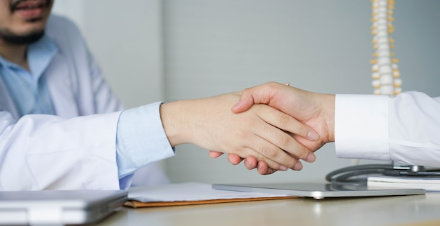 Close up specialist doctor man handshake with patient after completed checkup or consulting