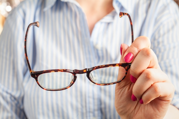 Close up spectacles with girl hand holding glasses on wood desk. release concept. spectacles selective focus.