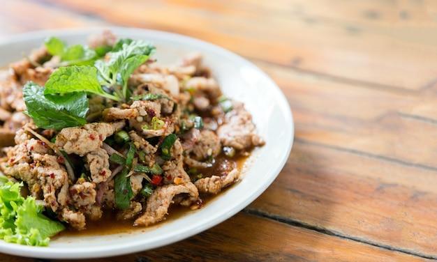 ハーブと血のソースで茹でたスパイシーな豚肉を木製のテーブルにクローズアップ