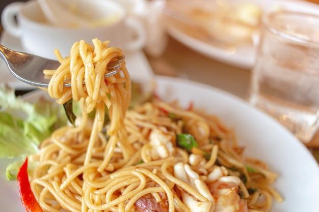 Close up spicy stir fried spaghetti on a fork