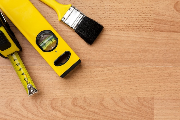 Close-up spirit level and brush on wooden background