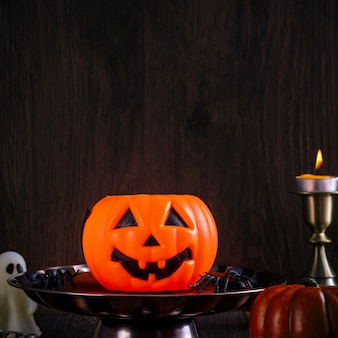 Close up of spooky halloween tricks, concept of horror festival decor, pumpkin lantern with candlestick and smoke.