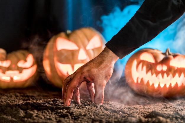 Close-up spooky hand and pumpkins arrangement