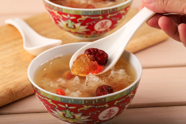 Close up spoon with peach gum collagen dessert is a chinese traditional refreshment beverages. it is contains bird nest, red dates, snow fungus, goji berry.