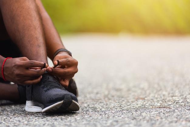 ジョギングの準備をしてランニングシューズを試してみて靴紐に座ってスポーツランナーの黒人男性を閉じる