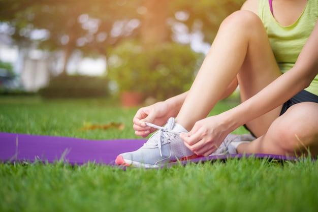 Конец вверх женщина спорта связывает ботинки снаружи