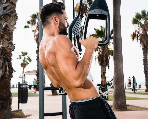 Крупным планом спортивный человек делает подтягивания