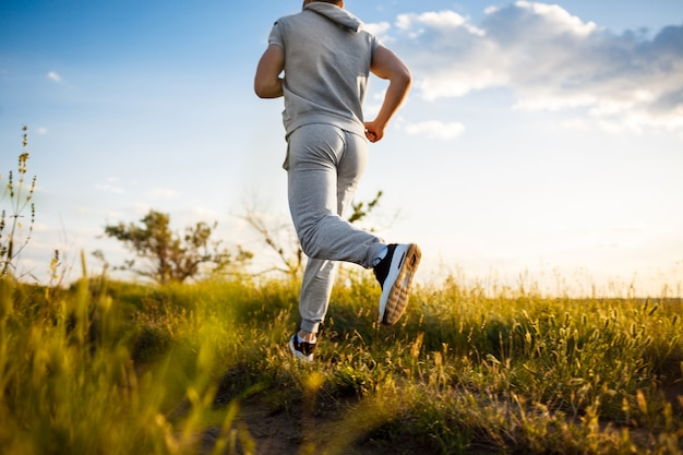 Close up of sportive man jogging in field at sunrise.