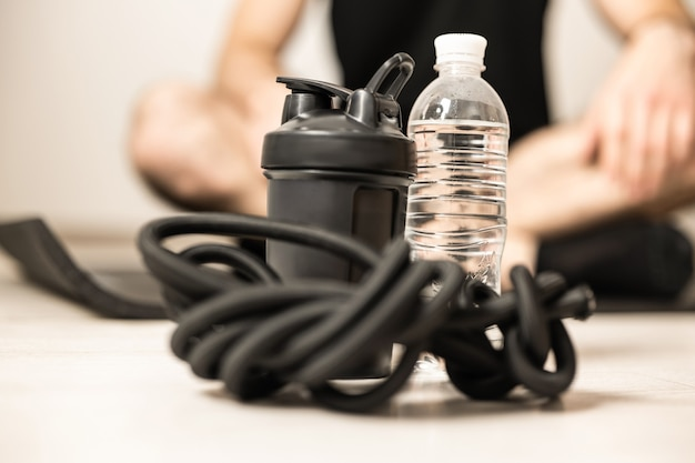 Close up sports equipment. sports bottle, plastic water bottle, resistance band. blurred man in easy seat pose sitting with crossing legs. workout at home. wellbeing and activity concept.