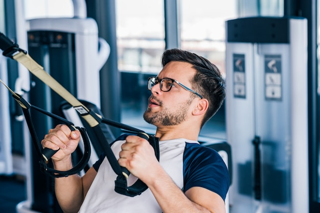 Close-up of sportsman in eyeglasses working out on trx.