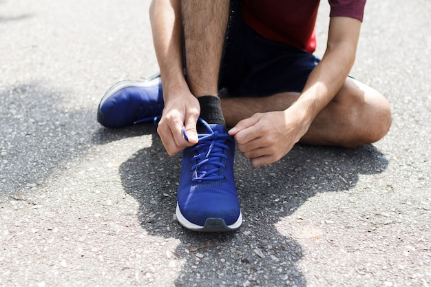 Close-up of sportsman. he tying sneakers on running shoes before practice.