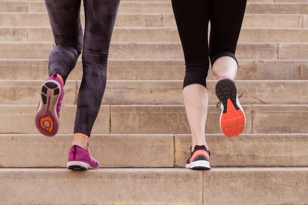 Close-up of sportswomen climbing stairs