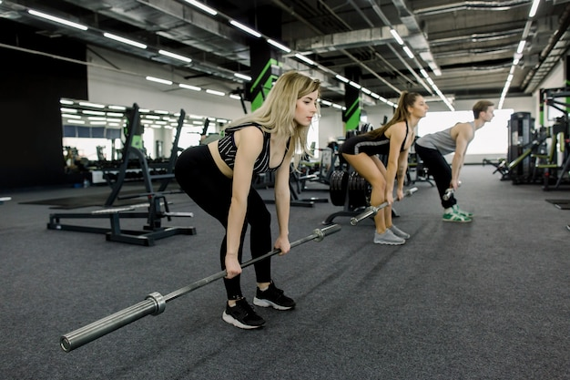Premium Photo   Close-up - sporty athletic man and women training with  barbells. cross fit training. young people during workout in gym. strength  training, powerlifting and sports.