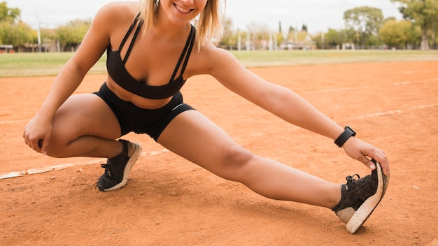 Close up of sporty woman stretching on stadium track