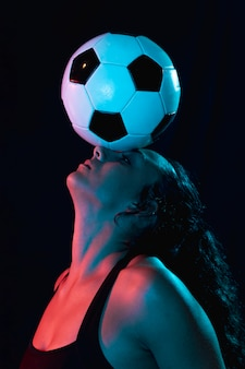 Close-up sporty woman with soccer ball