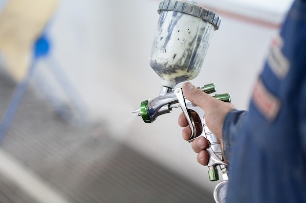 Close-up of a spray gun with white paint for painting a car in a special booth