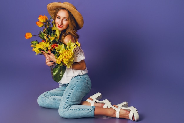Close up spring portrait of  beautiful blonde young lady in stylish straw summer hat holding   colorful spring flower bouquet   near  purple wall background.