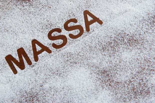 Close up on sprinkled flour with the word massa written