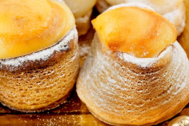 Close-up of sprinkled sugar cream pies.