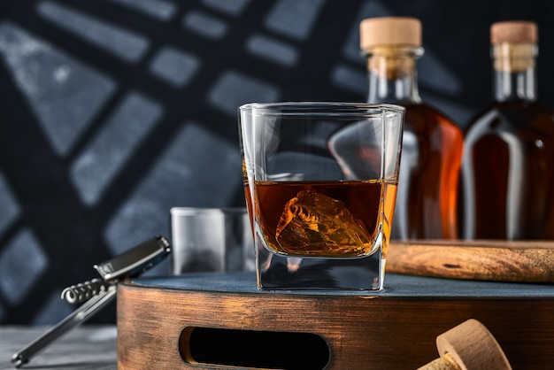 Close up of a square glass of whiskey with ice