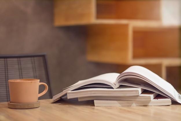 木製のテーブルにコーヒーのスタックブックと茶色のカップを閉じます