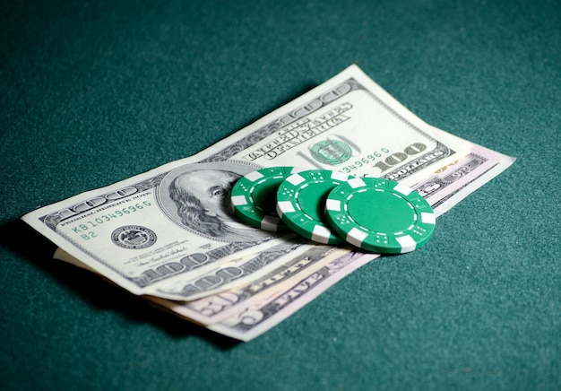Close-up stack of casino chips and dollar bills on the poker table