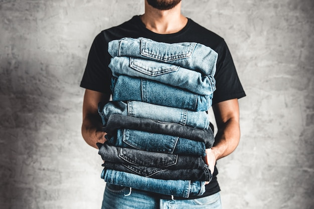 Close up stack of folded denim blue jeans in hand over gray wall background, copy space