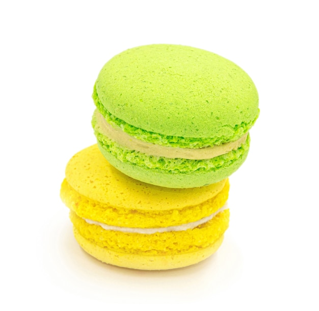 Close up of stack of green and yellow macaron cookies isolated on white