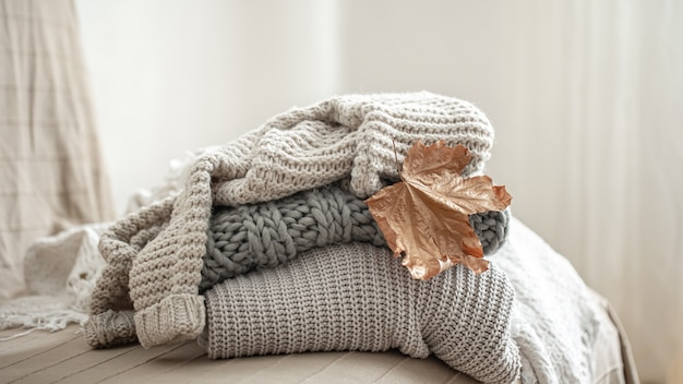 Close-up of a stack of knitted sweaters on a blurred background.