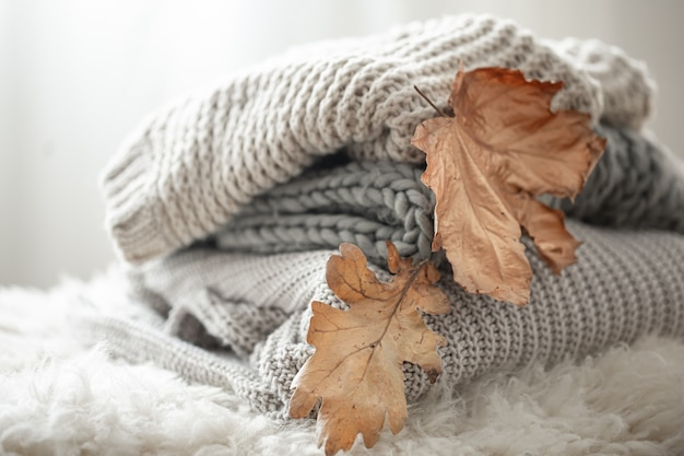Close-up of a stack of knitted sweaters with autumn leaves on a blurred background.