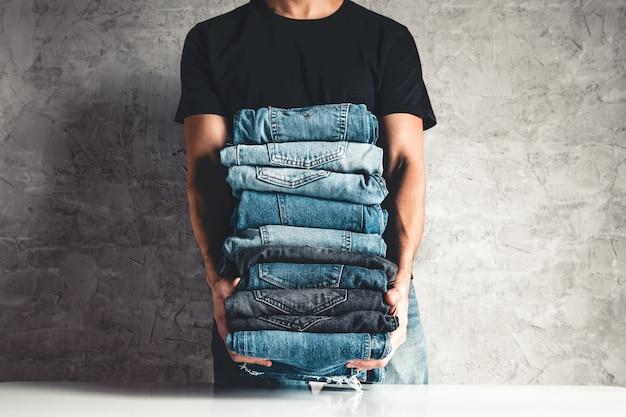 Закройте стопку свернутых джинсовых синих джинсов в руке на сером фоне стены, скопируйте пространство