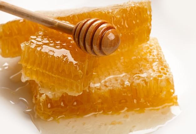 흰색 배경에 분리된 접시에 신선한 자른 황금색 빗 꿀 조각과 천연 나무 디퍼의 스택을 닫고 높은 각도 보기