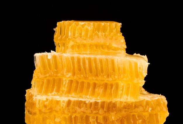 검정색 배경, 낮은 각도, 측면 보기에 격리된 접시에 몇 개의 신선한 절단된 황금 빗 꿀 조각 스택을 닫습니다.