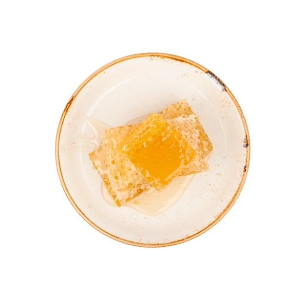 흰색 배경에 분리된 접시에 갓 자른 황금색 빗 꿀 조각 몇 개를 닫고 바로 위에 있는 위쪽 보기