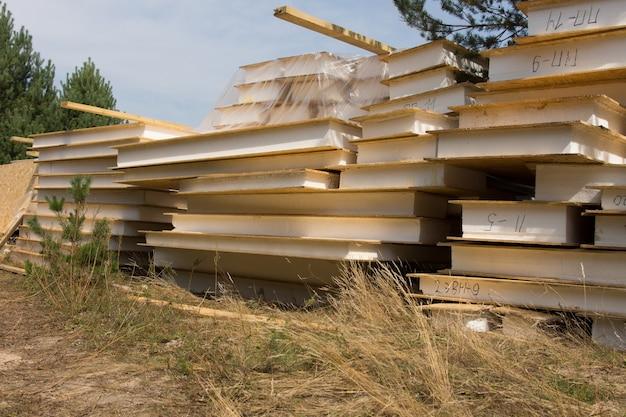 Закройте штабелированных строительных материалов, готовых для строительства дома недвижимости, сложенных на травянистом ландшафте на месте проекта.
