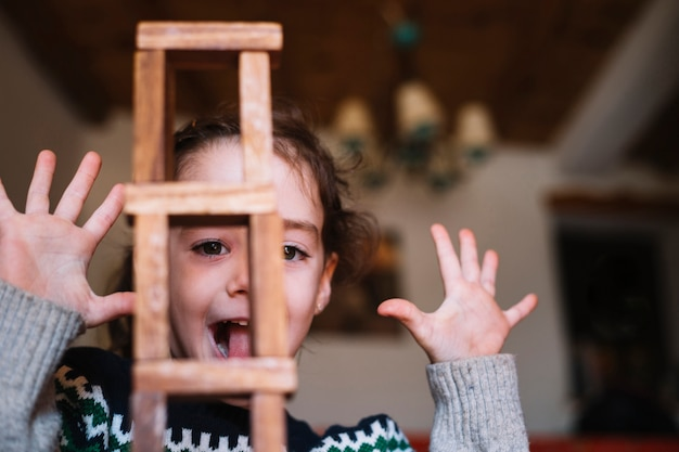 Close-up of stacked wooden blocks in front of excited girl