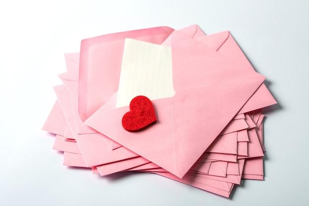 ピンクの封筒とメールレターペーパーと赤い目隠しの積み重ねを閉じる