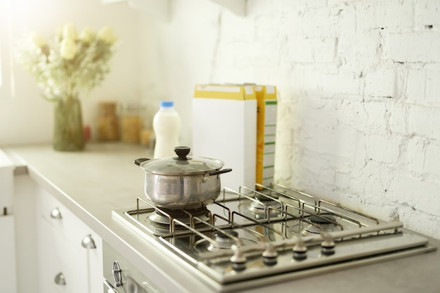 Close up of stainless steel cooking pot on gas stove in contemporary modern home kitchen. selective focus. morning, cooking breakfast concept