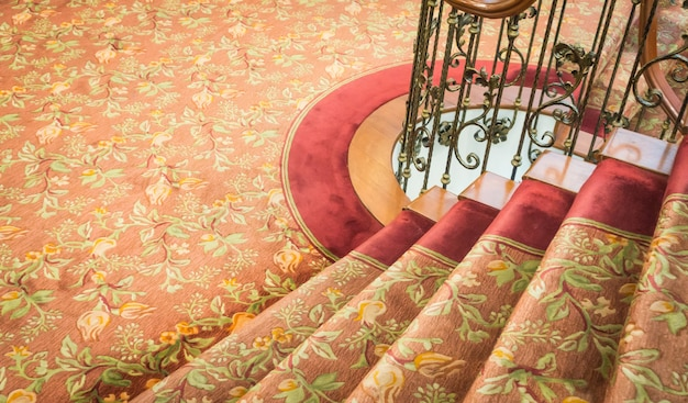Close up of staircase covered with carpet .