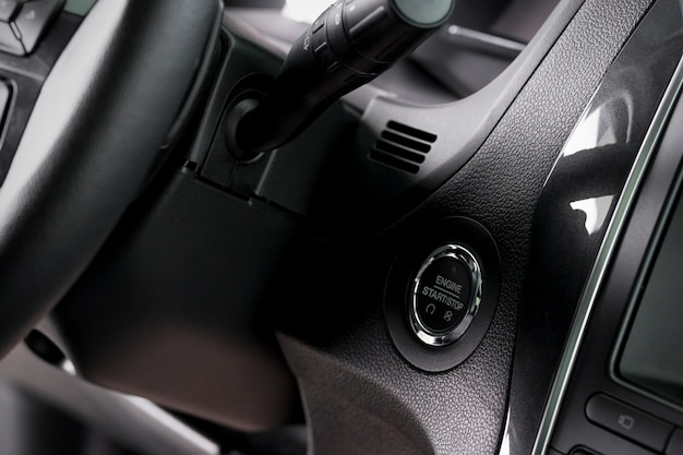Close up start stop button and windscreen wiper switch inside a new car
