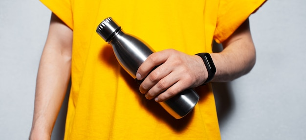 Close-up of steel reusable thermo water bottle in male hands.