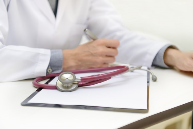 Close-up of stethoscope and paper on background of doctor
