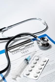 Крупным планом стетоскоп с таблетками и шприц на столе