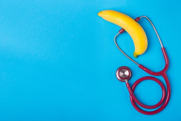 Close up stethoscope and yellow banana on blue background