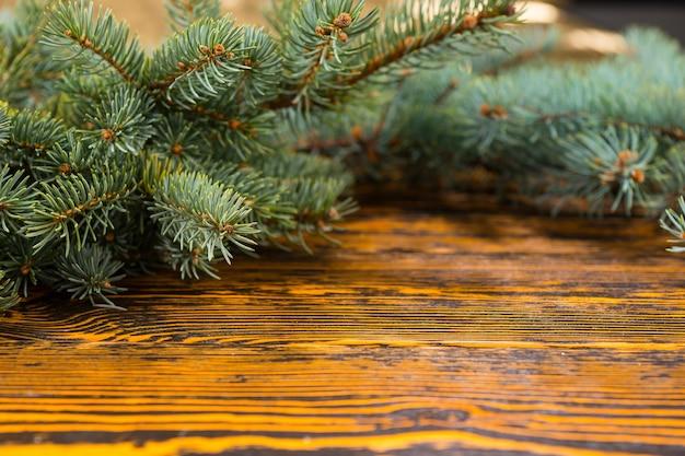 木目と選択的な焦点で素朴な木製のテーブルのコピースペースをフレーミングするお祝いの常緑の枝の静物をクローズアップ