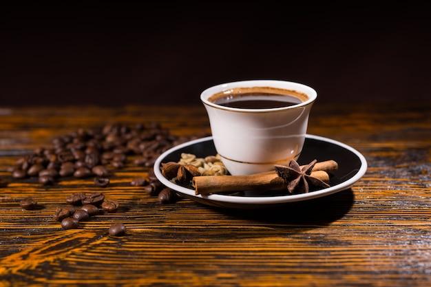 Крупным планом натюрморт с белой чашкой и блюдцем со свежесваренным кофе на деревенской деревянной столешнице, усыпанной жареными кофейными зернами, палочками корицы и звездчатым анисом