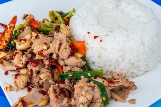 Close up stir fried minced chicken and basil with jasmine rice on table